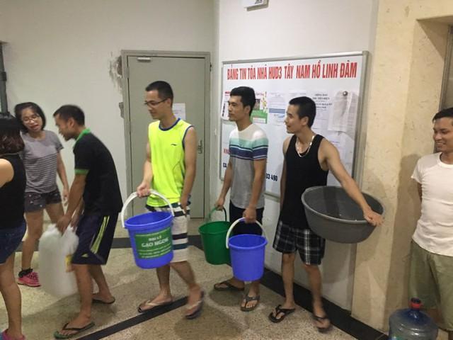 Người dân dùng xô chậu đi sách từng thùng nước về sinh hoạt (ảnh cư dân cung cấp).