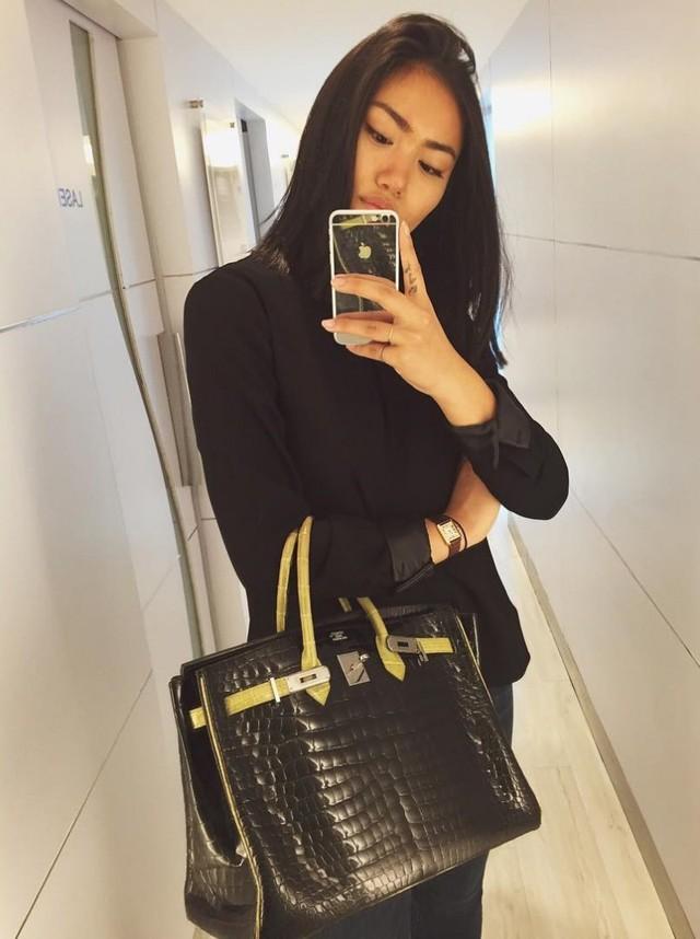 Bạn có thể chú ý đến chiếc iPhone mạ vàng của cô gái này, tuy nhiên nó chẳng là gì so với chiếc túi Hermes Crocodile Skin Birkin Bag trị giá 100.000 USD kia.