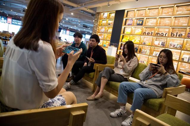 Nhân viên chơi game trên điện thoại tại trụ sở Netmarble ở Seoul. Ảnh: Bloomberg.