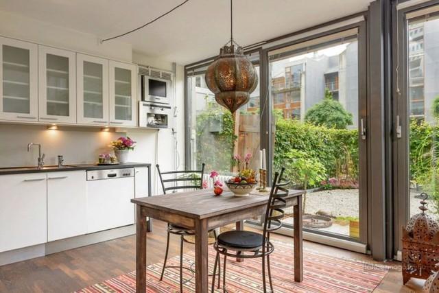 Nhờ những tấm cửa kính rộng mở và cao sát trần phía cuối nhà mà chủ nhà có thể ngắm sân vườn từ bếp và phòng khách.