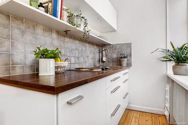 Khu bếp nhỏ nhắn được thiết kế hiện đại, đẹp mắt với cây xanh và hệ thông tủ kệ khép kín.