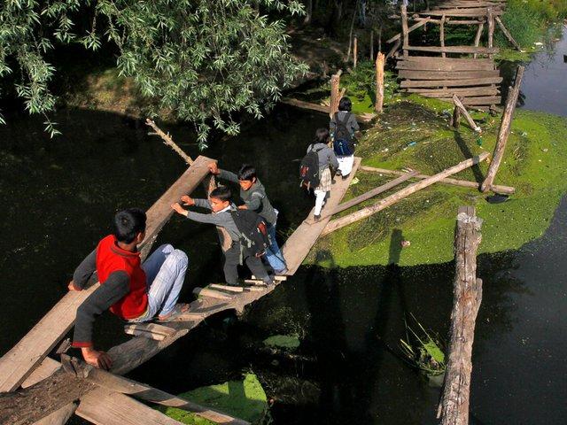 Những tấm ván gỗ mỏng manh đưa học sinh tới lớp ở Kashmir, Ấn Độ. Câu cầu gỗ trước đây đã bị lũ quét cuốn trôi 1 phần.