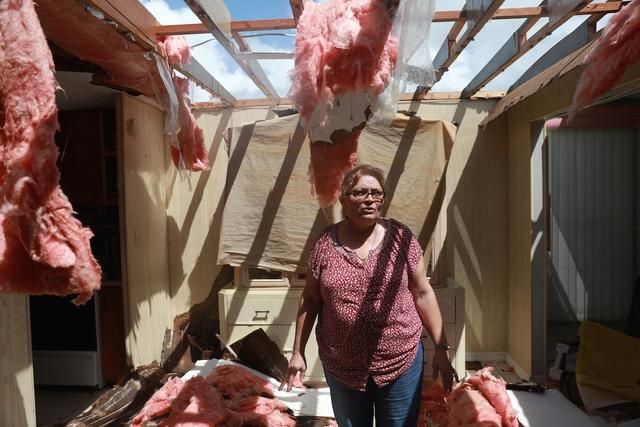 Maida Esteves, một người dân sinh sống trong những ngôi nhà di động đang đứng trong phòng khách đã bị phá hủy.