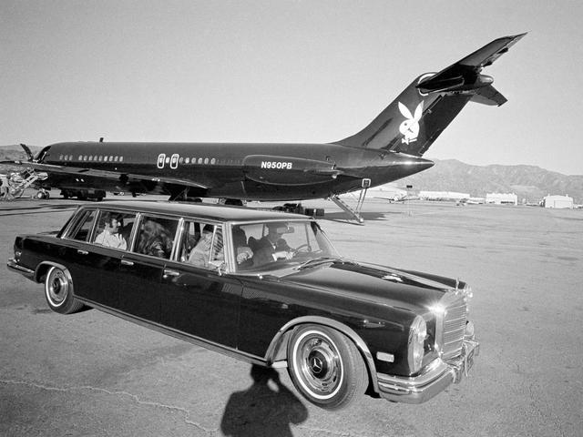 Hugh Hefner trong chiếc xe Mercedes-Benz limousine với nền là phi cơ Playboy nổi bật.