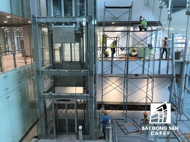 Đội ngũ công nhân đang lắp kính và vận hành thử hệ thống thang máy bên trong nhà ga.