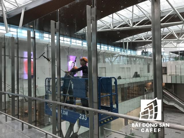 Đội ngũ công nhân đang lau chùi toàn bộ hệ thống kính tường bên trong nhà ga.