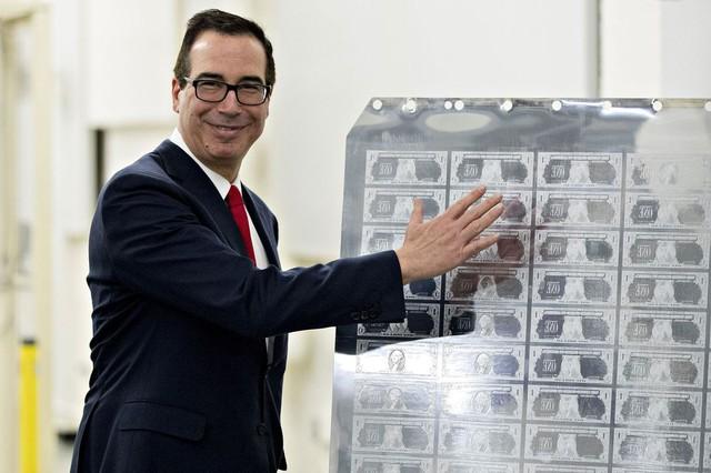 Ông Steven Mnuchin chụp ảnh cùng tấm phôi kim loại được dùng để in đồng 1 USD mới có chữ ký của ông. Đi cùng ông Mnuchin trong chuyến thăm là vợ cùng Jared Kushner, con rể Tổng thống Mỹ Donald Trump và nhiều quan chức.