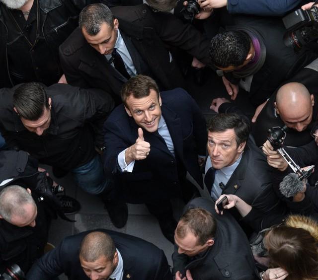 Kết quả thăm dò cho thấy ứng viên Macron - người đang mỉm cười và giơ ngón tay cái - sẽ chiến thắng. Ảnh: Getty Images.