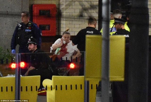 Một phụ nữ đang được các nhân viên cứu hộ giúp đỡ sau vụ tấn công khủng bố. Ảnh: Daily Mail.