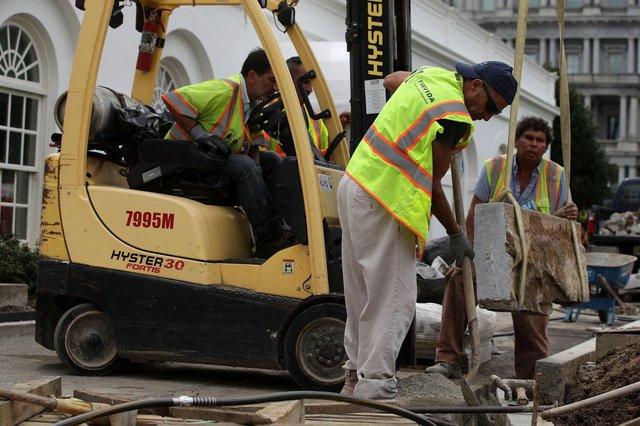 Công nhân xây dựng đưa những khối đá lớn xuống đất tại khu vực phía trước Cánh Tây công trình.