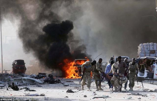 Binh sĩ quân đội cũng tham gia vào nỗ lực cứu hộ. Trong ảnh là một thành viên lực lượng quân đội vũ trang Somalia được đồng đội đưa khỏi hiện trường.
