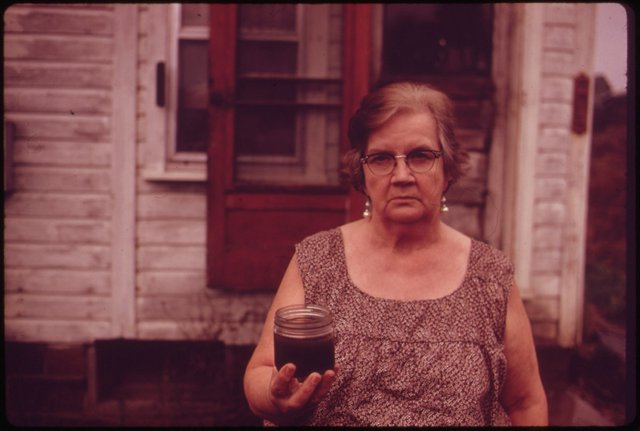 Bà Mary Workman sống ở Steubenville, Ohio. Trên tay bà là lọ chứa loại nước ô nhiễm nghiêm trọng múc lên từ dưới giếng. Người phụ nữ này từng đệ đơn kiện công ty khai thác than gần đó vì cho rằng nó gây ô nhiễm giếng nước nhà bà. Ngày nay, nước Mỹ có những đạo luật nghiêm ngặt để bảo vệ nguồn nước ngầm khỏi bị ô nhiễm.