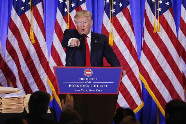 Trump chỉ tay và phóng viên CNN và gọi đài này là hãng tin giả. Ảnh: Reuters.