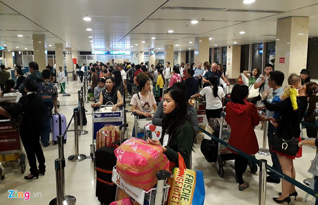 Chiều muộn 12/1, hành khách xếp hàng dài tại các quầy check-in bên trong sân bay Tân Sơn Nhất. Khu vực làm thủ tục của Vietnam Airlines đông đúc nhất.