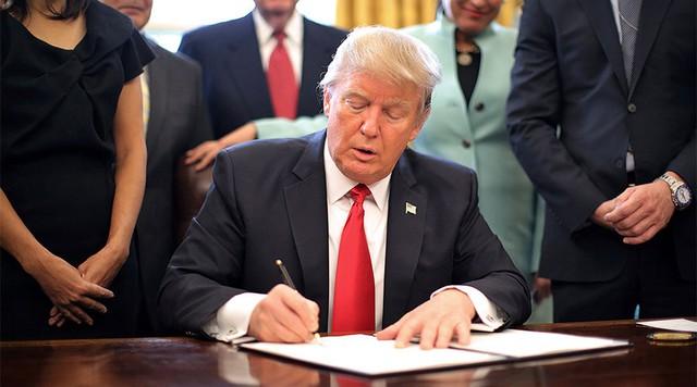 Tổng thống Donald Trump ký sắc lệnh hạn chế người tị nạn nhập cư đối với các công dân đến từ bảy quốc gia Hồi giáo. Ảnh: Reuters