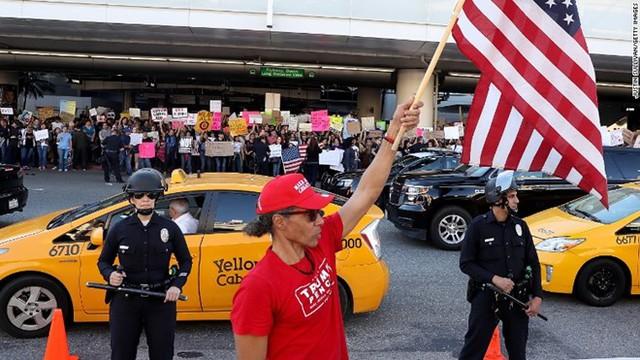 Một người đàn ông ủng hộ lệnh cấm của ông Trump vẫy cờ Mỹ trước đám đông biểu tình phản đối sắc lệnh tại sân bay Los Angeles hôm 29/1. Ảnh: Getty.