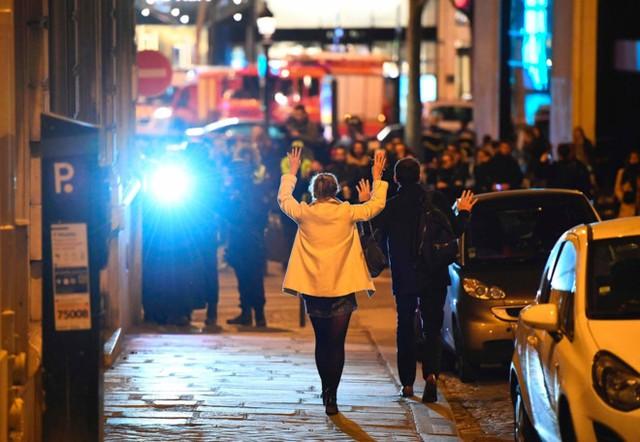 Những người đi đường giơ tay tiến về hướng cảnh sát. Ảnh: Getty.