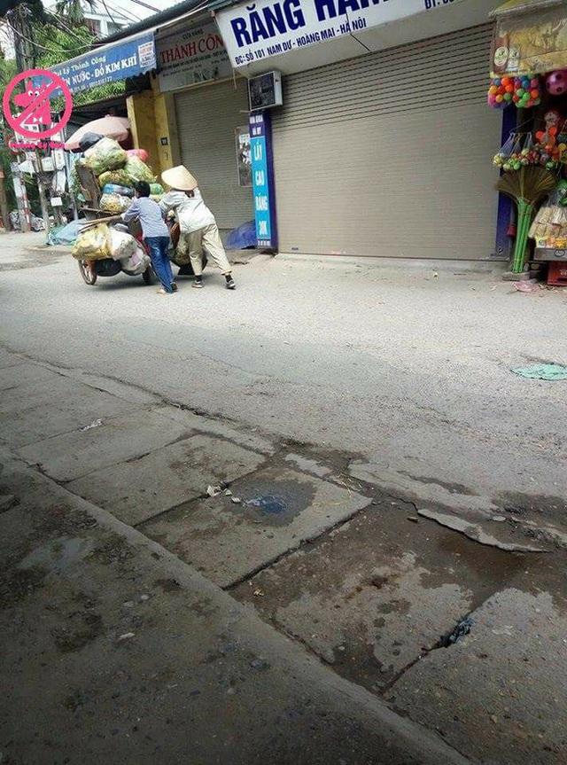 Cậu bé theo mẹ đi làm rồi cùng mẹ đẩy chiếc xe rác trên đường. Nguồn: KSC.