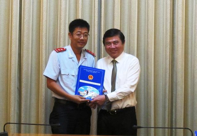 Chủ tịch UBND TP HCM Nguyễn Thành Phong (bìa phải) trao quyết định bổ nhiệm cho ông Trần Thanh Tùng