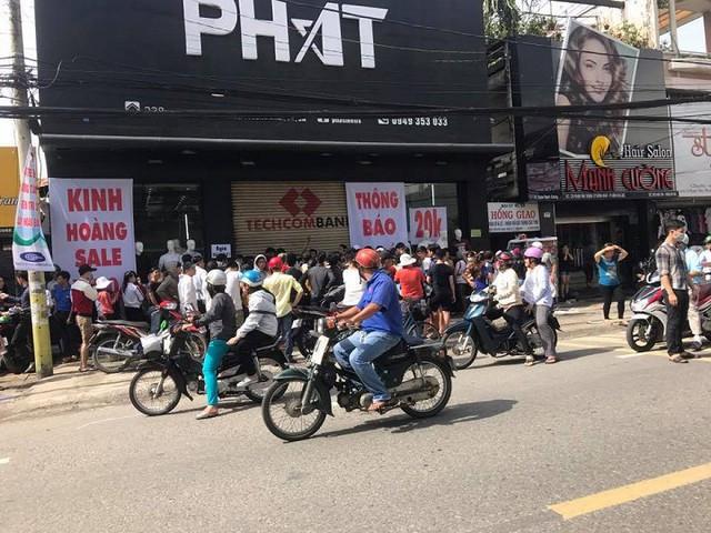 Người dân tập trung trước cửa hàng giảm giá sốc.