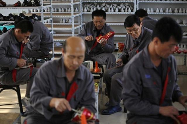 Công nhân Triều Tiên gia công giày thể thao tại một nhà máy ở TP Đan Đông. Ảnh: REUTERS
