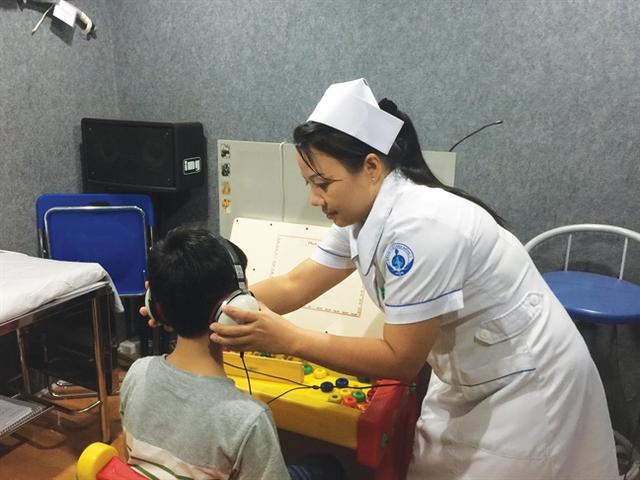 Một bé bị viêm tai giữa đang được kiểm tra chức năng nghe - Ảnh: Thanh Huyền