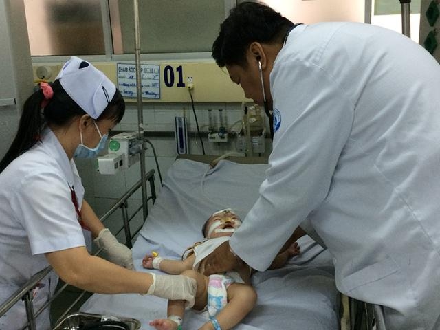 Bác sĩ Đinh Tấn Phương, Trưởng khoa Cấp cứu Bệnh Nhi đồng 1 đang khám cho bệnh nhi.