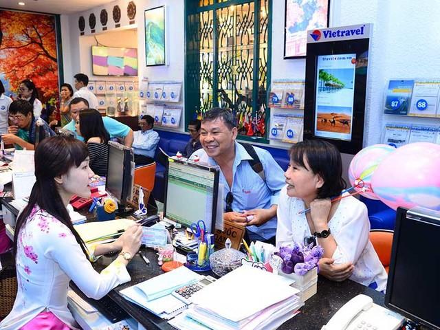 Du lịch trực tuyến đang là miếng bánh lớn. Trong ảnh: Khách hàng đang tìm hiểu, đăng ký du lịch trực tuyến tại một công ty lữ hành. ảnh: TÚ UYÊN
