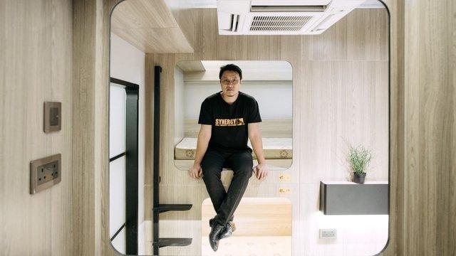 Keith Wong ngồi trên chiếc giường tầng bên trong một phòng của dự án Bibliotheque ở quận Yau Ma Tei, Hồng Kông.