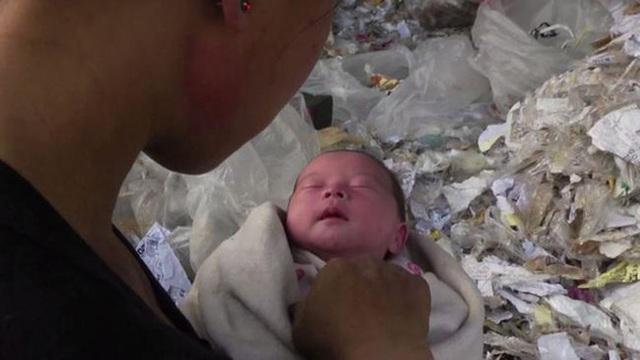 Người mẹ ôm con giữa rác thải ngồn ngộn trong phim tài liệu Plastic China. Ảnh: NEWS.COM.AU