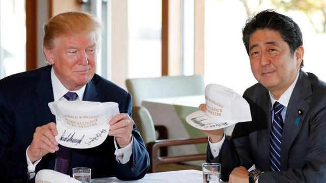 Tổng thống Trump và thủ tướng Abe cùng ký tên lên hai chiếc mũ có hàng chữ Donald và Shinzo làm Liên minh thậm chí còn vĩ đại hơn (Ảnh: Reuters)