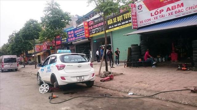 Lòng đường Nguyễn Hoàng trở thành nơi sửa xe ô tô. Ảnh Sỹ Lực