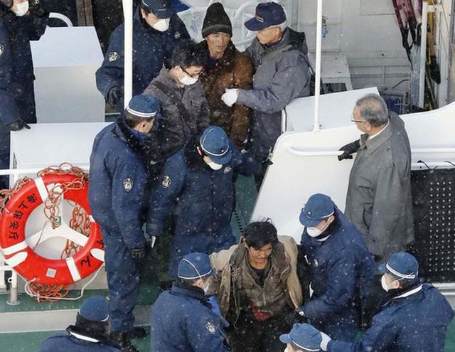 Cảnh sát Nhật đưa một nhóm thủy thủ khỏi một tàu Triều Tiên ở Hakodate hôm 9-12 Ảnh: KYODO