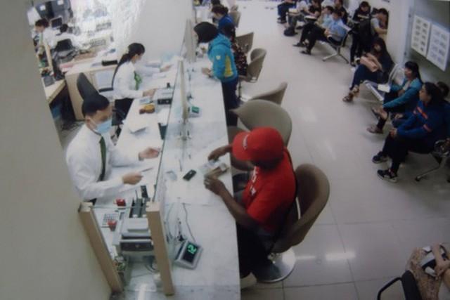 Một đối tượng đang dùng hộ chiếu giả mở tài khoản rồi rút tiền phi pháp Ảnh: Thuận Thiên