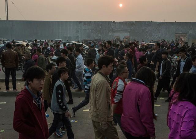 Công nhân nhà máy Foxconn tại Trịnh Châu rời nơi làm việc sau một ca đêm, những người còn lại bắt đầu ca làm việc ban ngày của mình. Ảnh: New York Times.