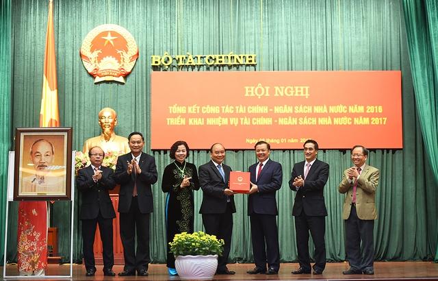 Thủ tướng Nguyễn Xuân Phúc tặng quà lưu niện cho Bộ Tài chính. Ảnh: VGP/Quang Hiếu