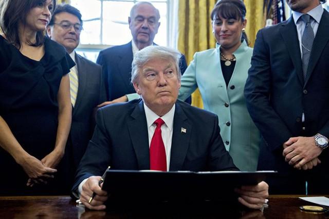 Tổng thống Trump ký sắc lệnh hành pháp ngăn chặn người nhập cư Hồi giáo vào Mỹ ngày 28/1. Ảnh: Bloomberg/Getty.