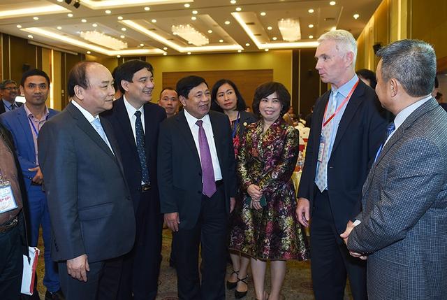 Thủ tướng trao đổi với các nhà đầu tư tham dự Hội nghị. Ảnh: VGP/Quang Hiếu