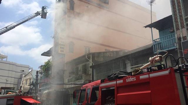 Lực lượng PCCC quận 6 tiếp cận với xe chữa cháy có thang đẩy nước phun lên cao để dập lửa.