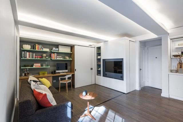 Lối vào giữa nhà phân căn hộ làm hai khu: một bên là phòng khách, phòng ngủ, phòng thay đồ. Khu vực bên kia là bếp và nhà tắm. Một bàn ăn nhỏ được đặt cuối nhà cạnh cửa sổ.