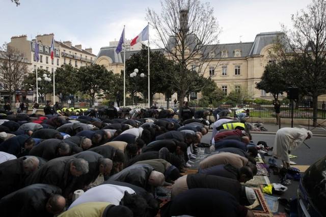 Người Hồi giáo cầu nguyện trên đường phố gần một thánh đường tại Paris, Pháp. Ảnh: AP.