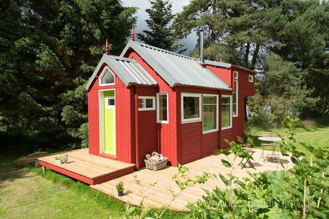 Ngôi nhà gỗ nhỏ nổi bật giữa thiên nhiên bao la cây cỏ nhờ màu sơn đỏ đẹp mắt.