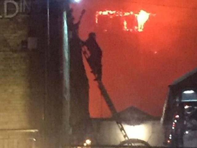 Một nhân viên cứu hỏa cố vào tầng trên của tòa nhà bị cháy. Ảnh: Twitter