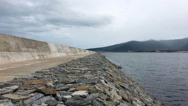 Ngăn cách giữa bãi tro xỉ với biển là đê chắn sóng bằng bê tông, cao hơn 6m