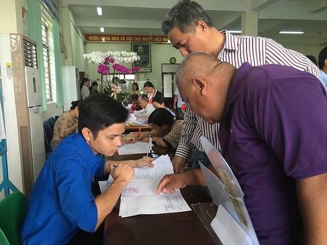 Cán bộ đang hướng dẫn người dân làm thủ tục xin cấp giấy chứng nhận nhà, đất ở quận 12 (TP.HCM). Ảnh: VIỆT HOA