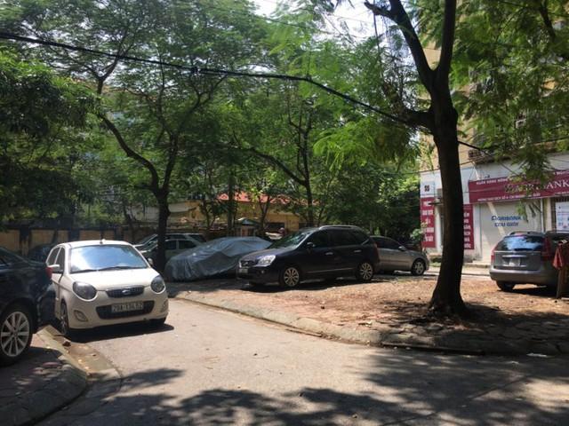 Nhiều ô tô đỗ bên trong khuôn viên khu tái định cư, có xe phủ bạt nhiều ngày.