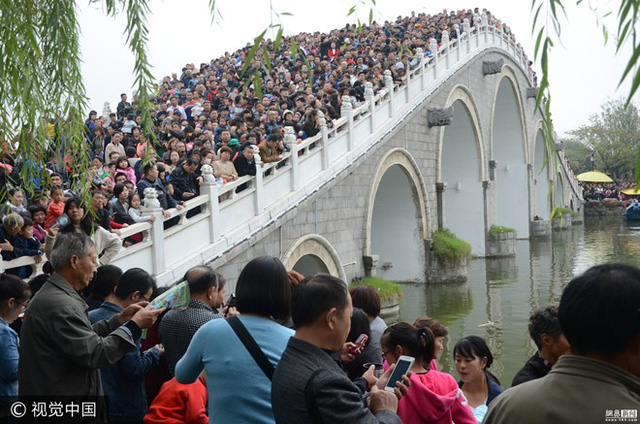 Hình ảnh này được ghi lại tại Vườn Thanh Minh Thượng Hà ở Khai Phong, Hà Nam (Trung Quốc) khi du khách đang xem biểu diễn trên một cây cầu. (Nguồn: 163)