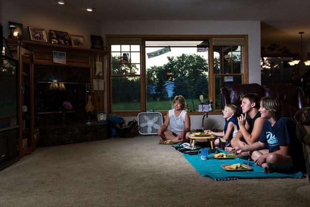 Một gia đình đi picnic dã ngoại trong nhà với một tấm chăn lớn lót ở phía trước TV.