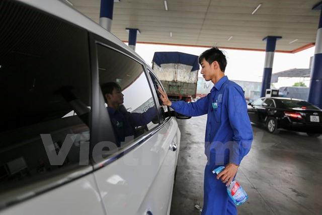 Nhân viên cây xăng ở xã Liên Bão, huyện Tiên Du, Bắc Ninh phục vụ làm sạch xe miễn phí cho khách đổ xăng. (Nguồn: Vietnam+)