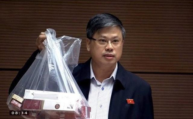 ĐB Nguyễn Sỹ Cương giơ cao túi lớn đựng thuốc lá khi phát biểu trước QH ngày 31-10 - Ảnh: Soha